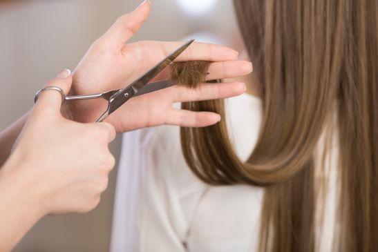 בחורה עם שיער חום שגוזרים לה במספריים את קצוות השיער