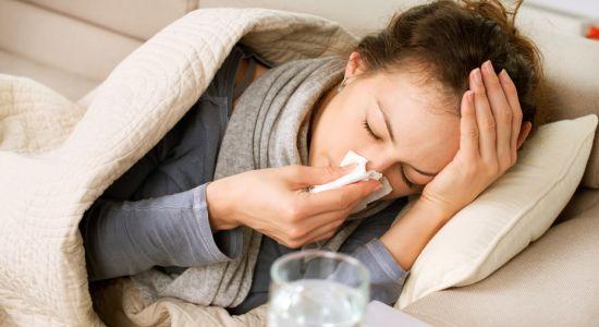 בחורה שוכבת על ספה ומקנחת את האף