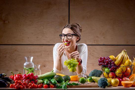 צריכה של פירות וירקות היא בסיס חיוני לתזונה נכונה, בחורה מחייכת עם מגוון פירות וירקות