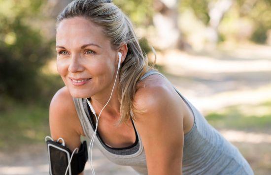 בחורה מחייכת עם אזניות במהלך פעילות גופנית
