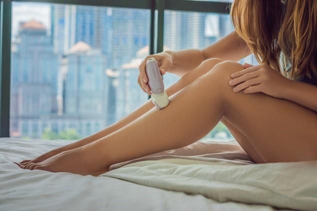 אישה מסירה שיער ברגליים