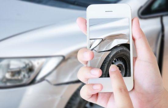 אדם מצלם את הרכב שלו לאחר תאונה