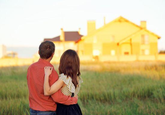 זוג מתחבק ומסתכל על בית
