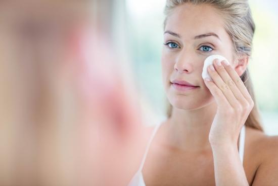 אישה מנקה את הפנים שלה