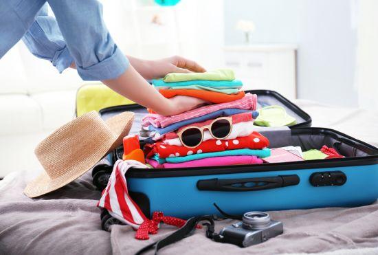 אישה אורזת בגדים במזוודה