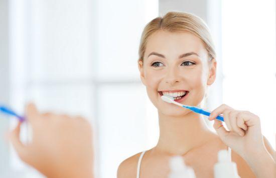 אישה מצחצחת שיניים