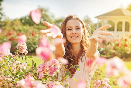 אישה עומדת בשדה עם פרחים
